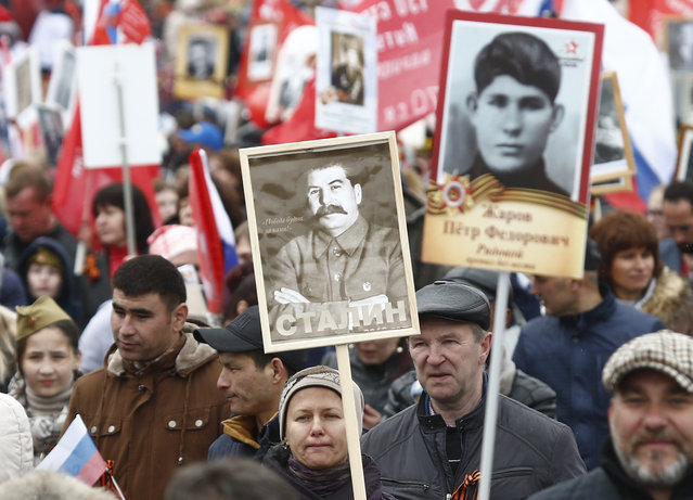 A woman holds a portrait of Soviet dictator Josef Stalin as she takes part in the Immortal Regiment march during the 72nd anniversary of the end of World War II on the Red Square in Moscow, Russia on May 9, 2017. (Photo by Maxim Shemetov/Reuters)