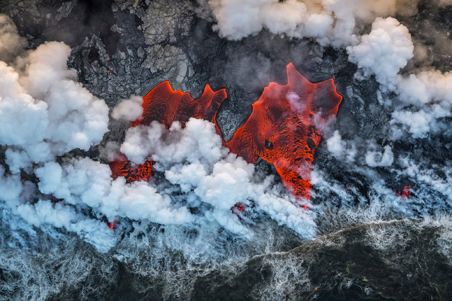 """Runner-up, landscapes: The red elephant – Luis Manuel Vilariño Lopez (Spain). """"May 2018 marked the beginning of the largest eruption of Kilauea volcano (Hawaii) for 200 years. The stream of lava covered a huge area, eventually reaching the ocean. I set myself the task of capturing the power and drama of these creational processes in photographs. The everchanging coast was the scene of a fierce battle between the ocean fighting for its lost space and the volcano. Clouds of acidic vapour rose above this clashing of the elements fed by giant waves the Pacific hurled up against the lava"""". (Photo by Luis Manuel Vilariño Lopez/2019 GDT European Wildlife Photographer of the Year)"""