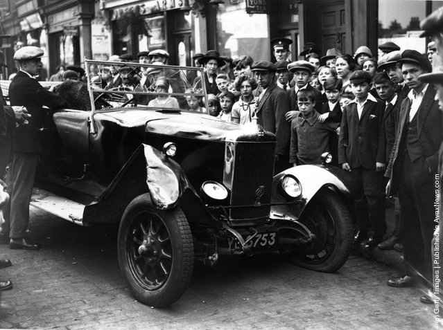 1926: A crowd of spectators in Stepney Green, east London, with one of the two cars which were involved in a crash there, killing two men and injuring a third