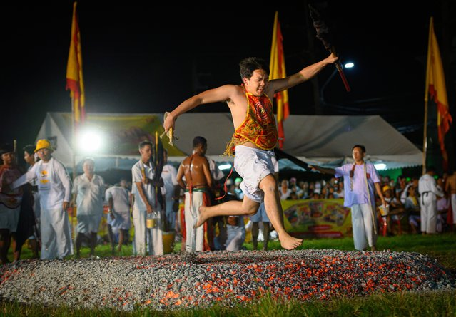 A devotee of a Chinese shrine walks on ambers during the annual Vegetarian Festival in Phuket on October 4, 2019. The festival begins on the first evening of the ninth lunar month and lasts for nine days, with many religious devotees slashing themselves with swords, piercing their cheeks with sharp objects and committing other painful acts to purify themselves, taking on the sins of the community. (Photo by Mladen Antonov/AFP Photo)