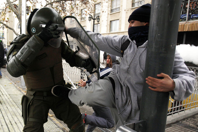 A protester kicks a policeman during a student demonstration in Santiago, Chile, Tuesday, June 10, 2014. Tens of thousands of students protested in Chile demanding education reform since President Michelle Bachelet took power on promises of deep changes. (Photo by Luis Hidalgo/AP Photo)