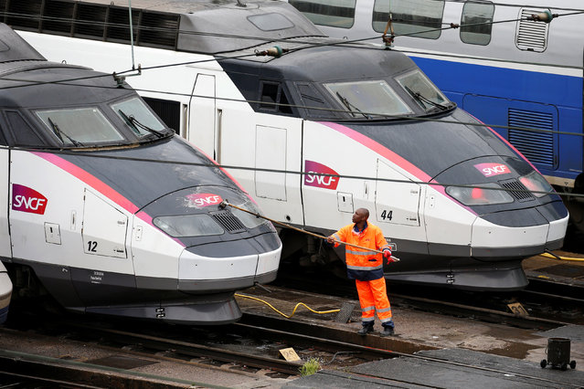 A worker cleans up a French TGV train (high speed train) parked at a SNCF depot station in Charenton-le-Pont near Paris, France, May 31, 2016 as railway workers from the France's rail-operator SNCF will start a national railway strike on Tuesday evening. (Photo by Charles Platiau/Reuters)