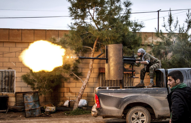 A fighter of the Kurdish People's Protection Units (YPG) fires an anti-aircraft weapon from Tel Tawil village in the direction of Islamic State fighters positioned in the countryside of the town of Tel Tamr, Syria, February 25, 2015. (Photo by Rodi Said/Reuters)