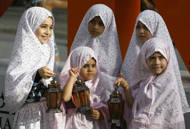 Lebanese girls hold traditional lanterns during street performances celebrating the upcoming Muslim holy month of Ramadan, in the southern port city of Sidon, Lebanon, Saturday, June 4, 2016. Devout Muslims throughout the world will begin to mark Ramadan next week, the holiest month in the Islamic calendar, refraining from eating, drinking, smoking and s*x from sunrise to sunset. (Photo by Mohammed Zaatari/AP Photo)