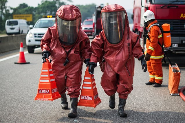 "Members of a Malaysian hazardous disaster emergency response team wearing protective suits take part in a trasportation emergency response drill ""Ex-Eagle"" on a highway near Bentong, outside Kuala Lumpur on June 24, 2014. The drill ensures transportation emergency incidents are managed in an effective and efficient manner. (Photo by Mohd Rasfan/AFP Photo)"