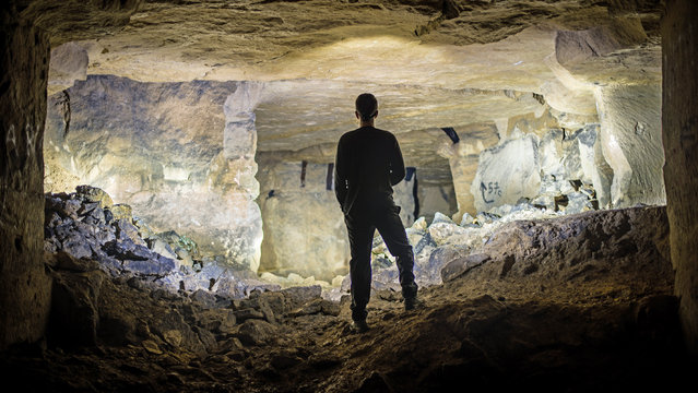 Box Freestone Mine, Wiltshire, U.K. Mike is shrouded in darkness and silhouetted against the sun as it shines through a hole in the derelict mine. (Photo by Mike Deere/Caters News)