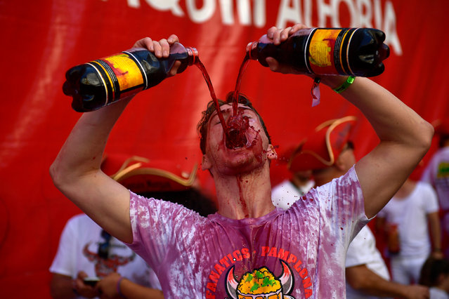 """Revellers drink wine as they start celebrating early while waiting for the launch of the """"Chupinazo"""" rocket, to celebrate the official opening of the 2019 San Fermin fiestas with daily bull runs, bullfights, music and dancing in Pamplona, Spain, Saturday July 6, 2019. (Photo by Alvaro Barrientos/AP Photo)"""