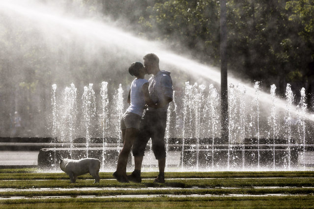 A couple kiss each other in front of water sprinklers as they walk the dog on a sunny morning near the Chancellery in Berlin, Wednesday, June 18, 2014. (Photo by Markus Schreiber/AP Photo)