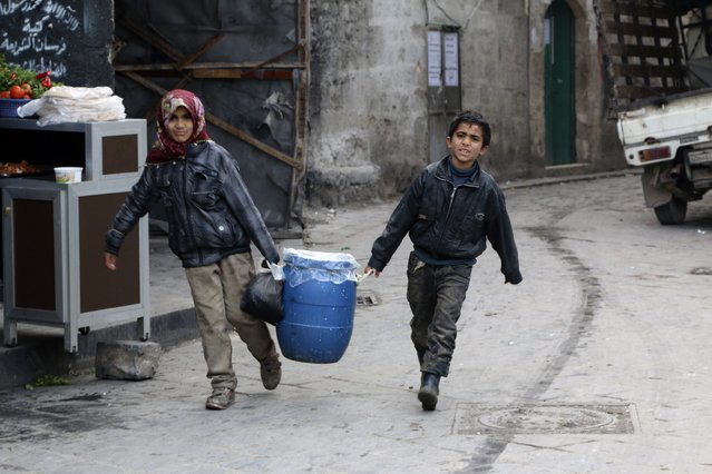 Children carry milk for sale in Old Aleppo January 1, 2015. (Photo by Mahmoud Hebbo/Reuters)