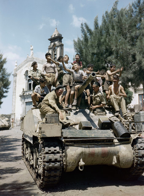 Children aboard a Sherman tank of the 3rd County of London Yeomanry in Sicily, August 1943. (Photo by IWM/PA Wire)