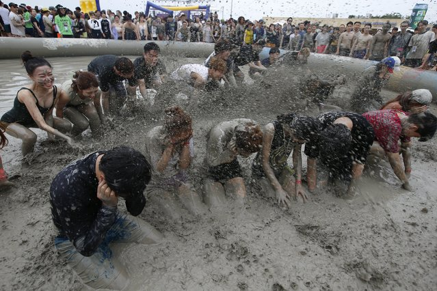 Festival-goers take a bath in a mud pool during the 20th Boryeong Mud Festival on Daecheon beach in Boryeong City, some 190 kilometers west of Seoul, South Korea, 22 July 2017. (Photo by Jeon Heon-Kyun/EPA/EFE)