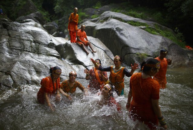 "Hindu devotees take a dip at the Bagmati River as they participate in the ""Bol Bom"" (Say Shiva) pilgrimage in Kathmandu July 21, 2014. The faithful, chanting the name of Lord Shiva, run about 15 km (9 miles) barefooted toward Pashupatinath temple seeking good health, wealth and happiness. (Photo by Navesh Chitrakar/Reuters)"