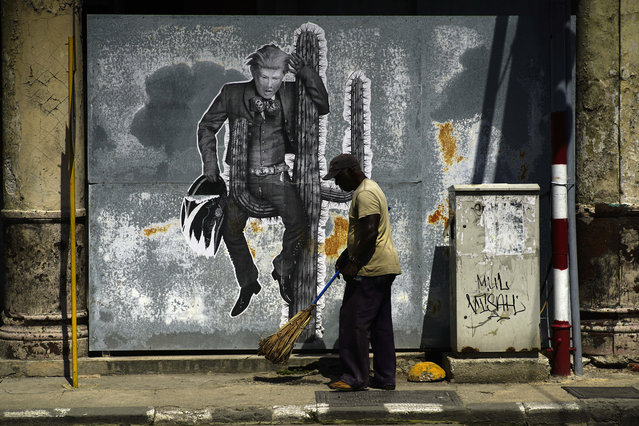 A street sweeper cleans the sidewalk under a mural painting depicting U.S. President Donald Trump, in Havana, Cuba, Friday, June 16, 2017. President Trump is en route to Miami, where he'll announce his plans for halting the flow of U.S. cash to Cuba's military and security services while maintaining diplomatic relations, in a partial reversal of the Obama administration policies. (Photo by Ramon Espinosa/AP Photo)