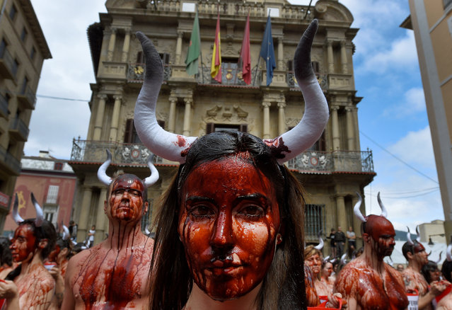 Animal rights protesters covered in fake blood demonstrate for the abolition of bull runs and bullfights a day before the start of the famous running of the bulls San Fermin festival in Pamplona, northern Spain, July 5, 2016. (Photo by Eloy Alonso/Reuters)