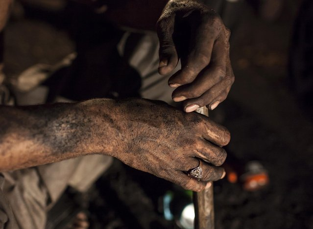 A miner covered in coal dust sits inside a mine in Choa Saidan Shah, Punjab province, April 29, 2014. (Photo by Sara Farid/Reuters)