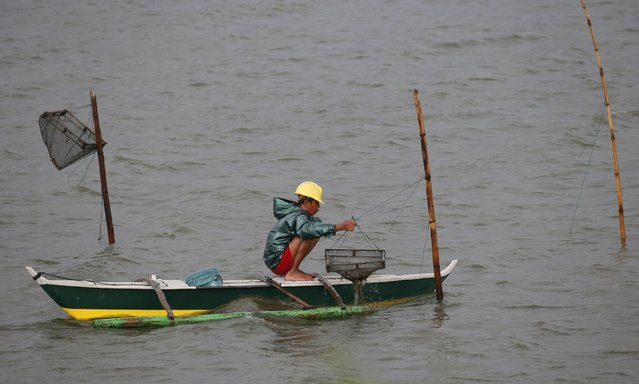 A resident checks his fish traps as he fishes amidst bad weather at the mouth of Manila Bay in Bacoor, Cavite August 21, 2015. The Philippine Atmospheric, Geophysical and Astronomical Service Administration (PAGASA) state weather bureau reported on Friday that Typhoon Goni maintained its strength of maximum winds of 170 kilometers per hour (kph) near the center and gustiness of up to 205 kph. (Photo by Erik De Castro/Reuters)