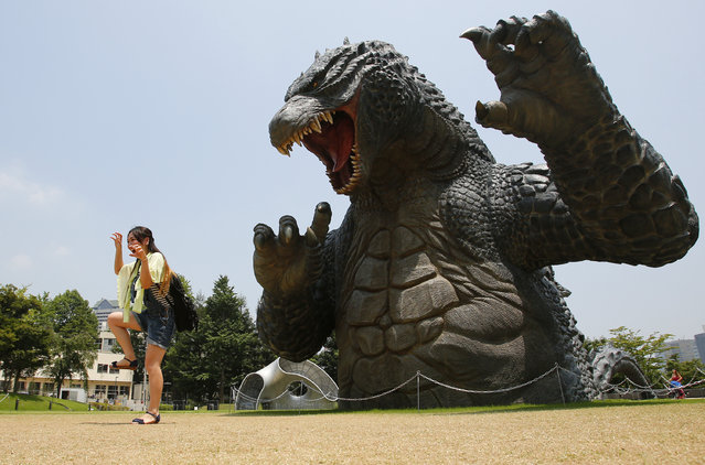 """A woman poses with a scaled down model of the new """"Godzilla"""", at Tokyo Midtown in Tokyo, Thursday, July 31, 2014. (Photo by Shizuo Kambayashi/AP Photo)"""