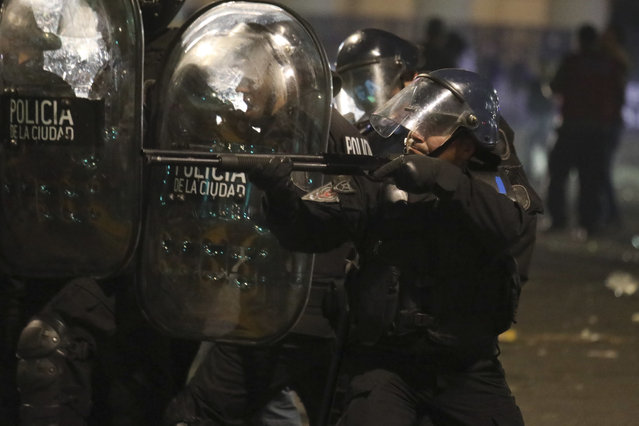 A police officer aims his shotgun at demonstrators during clashes after a protest for missing activist Santiago Maldonado, in Buenos Aires, Argentina, Friday, September 1, 2017. Human rights groups say Maldonado went missing a month ago today, after Argentine border police captured him during an operation against Mapuche Indians who were blocking a highway in Argentina's Patagonia. (Photo by Joaquin Salguero/AP Photo)