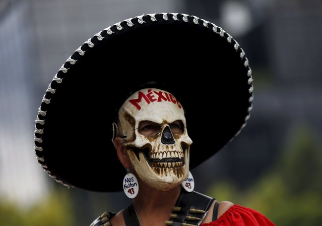 "A demonstrator wearing a skull mask takes part in a protest to mark the eleven-month anniversary of their disappearance in Mexico City, Mexico August 26, 2015. The students' disappearance on the night of September 26, 2014 in the southwestern city of Iguala triggered massive protests in Mexico and calls for justice. Officials say they were abducted by corrupt police officers, who handed them over to a local drug gang.  The words the earring read: ""We are missing 43"". (Photo by Henry Romero/Reuters)"