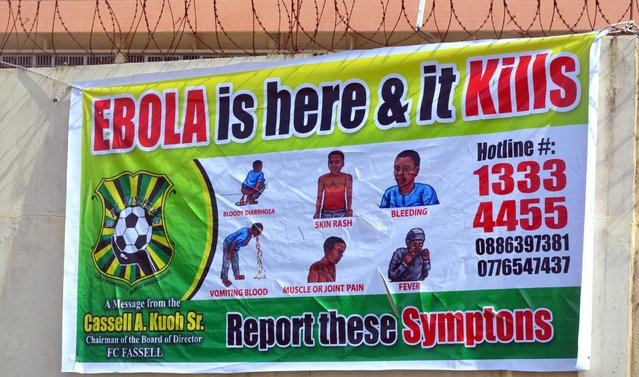 A picture taken on August 19, 2014 in Monrovia show an Ebola information billboard displayed near the John F Kennedy memorial medical centre where 17 Ebola patients, who had fled an attack on their clinic, were transferred to. (Photo by Zoom Dosso/AFP Photo)