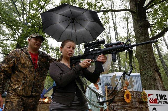 A member from the Belarussian pro-government youth organisation takes aim at balloons with an air gun during their annual meeting in a forest, near the village of Dumanovshchina, southeast of Minsk, August 16, 2014. Through this camp, the group aims to promote patriotism and instil moral values into youth. (Photo by Vasily Fedosenko/Reuters)