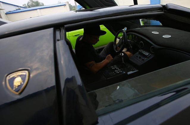 Wang Yu gets in a handmade replica of Lamborghini Diablo before a test drive outside a garage on the outskirts of Beijing, August 21, 2014. (Photo by Petar Kujundzic/Reuters)