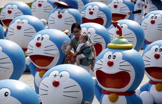 A woman poses with her baby among dolls featuring the Japanese animation character Doraemon during an exhibition at a department store in Seoul, South Korea, Monday, August 31, 2015. The exhibition is held to celebrate the nine year of opening of the department store, placing about 100 dolls of Doraemon at the mall. (Photo by Ahn Young-joon/AP Photo)