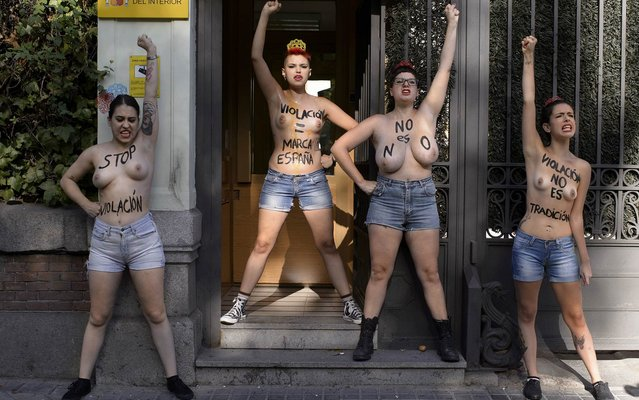 "Spanish leader of feminist movement FEMEN Lara Alcazar (L) and other members gestures during a demonstration staged in front the Ministry of the Interior in Madrid on August 28, 2014. Written on their bodies you can read ""Stop rape"", ""Rape=Spanish brand"", ""No is no"" and ""Rape, is not a tradition"". (Photo by Dani Pozo/AFP Photo)"