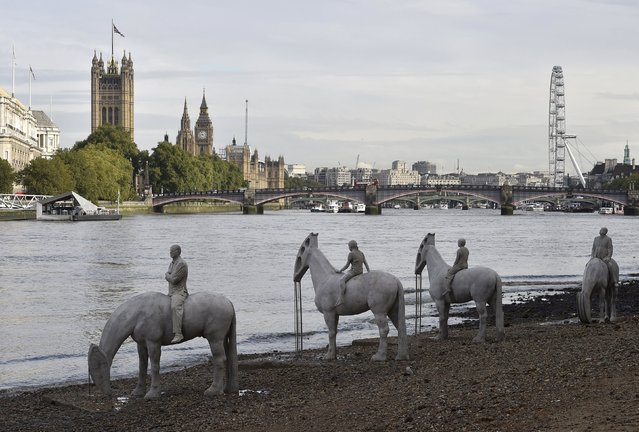 "Sculptures entitled ""The Rising Tide"" by British sculptor Jason deCaires Taylor are seen beside the River Thames in front of the Houses of Parliament and the London Eye ferris wheel in London, September 3, 2015. The representations of four horses and riders are fully visible at low tide but become immersed underwater twice a day as the Thames rises to reach full tide. The installation will be on display throughout September as part of the annual Totally Thames festival. (Photo by Toby Melville/Reuters)"