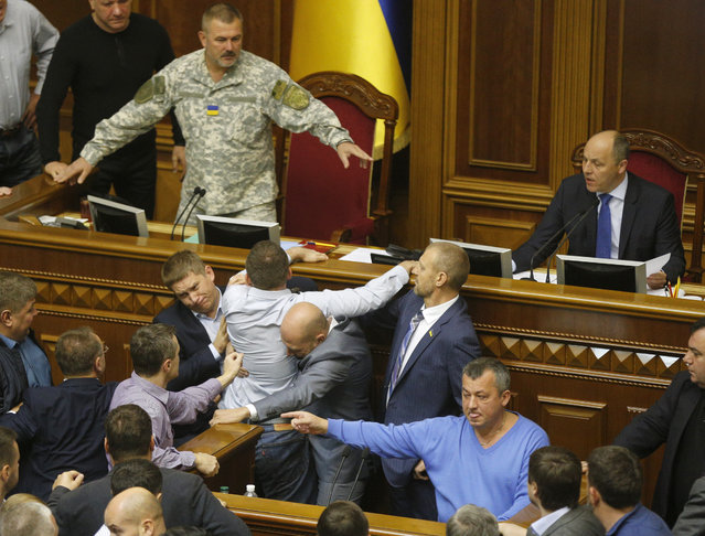 Ukrainian lawmakers scuffle during a parliament session in  the Ukrainian parliament, in Kiev, Ukraine, Friday, October 6, 2017. The parliament was forced to adjourn its session amid scuffles over hotly-disputed bills regarding the rebel-controlled eastern territories. (Photo by Efrem Lukatsky/AP Photo)