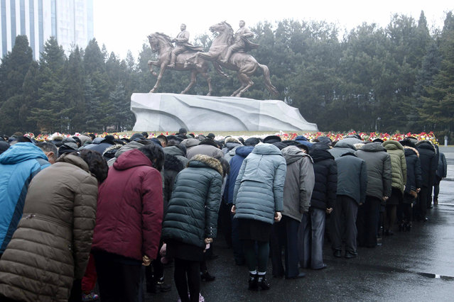 North Koreans bows in front of the bronze statues of their late leaders Kim Il Sung, left, and Kim Jong Il at the Mansudae Art Studio in Pyongyang, North Korea, Tuesday, December 17, 2019. North Koreans mark the eighth death anniversary of Kim Jong Il with usual floral offerings at the foot of the giant statues of the late leader. (Photo by Cha Song Ho/AP Photo)
