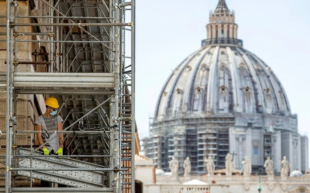 A worker on scaffolding wears a protective face mask in St. Peter's square during the Phase 2 of Covid-19 emergency, Rome, Italy, 05 May 2020. The Italian government is gradually lifting the lockdown restrictions that were implemented to stem the widespread of the Sars-Cov-2 coronavirus causing the COVID-19 disease. (Photo by Massimo Percossi/EPA/EFE)