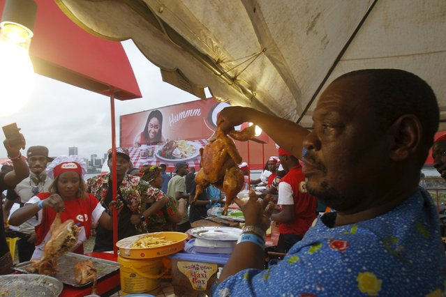 A cook shows a grilled chicken to visitors during the Festival des Grillades, in the yard of the Culture Palace of Abidjan, September 6, 2015. (Photo by Luc Gnago/Reuters)
