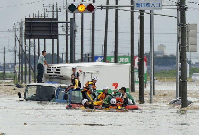 People are rescued from vehicles by firefighters at an area flooded by the Kinugawa river, caused by typhoon Etau, in Joso, Ibaraki prefecture, Japan, in this photo taken by Kyodo September 10, 2015. (Photo by Reuters/Kyodo News)