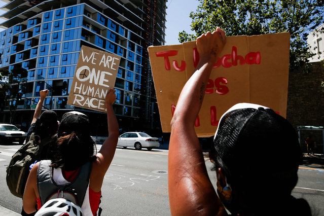 People hold up signs on East Santa Clara Street during a demonstration over the police killing of George Floyd in downtown San Jose, Calif., on Wednesday, June 3, 2020. (Photo by Randy Vazquez/Bay Area News Group)