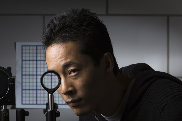 University of Rochester Ph.D. student Joseph Choi demonstrates a cloaking device using four lenses in Rochester, New York in this September 11, 2014 University of Rochester handout photo. Scientists at the University of Rochester have discovered a way to hide large objects from sight using inexpensive and readily available lenses, a technology that seems to have sprung from the pages of J.K. Rowling's Harry Potter fantasy series. (Photo by J. Adam Fenster/Reuters/University of Rochester)