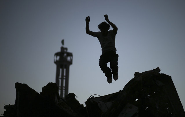 A Palestinian youth practices his Parkour skills over the ruins of houses, which witnesses said were destroyed during a seven-week Israeli offensive, in the Shejaia neighborhood east of Gaza City October 1, 2014. (Photo by Mohammed Salem/Reuters)