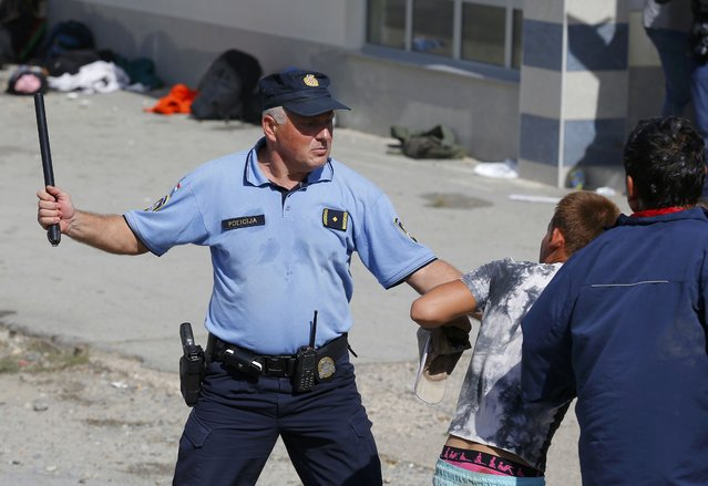 A policeman intervenes as Syrian and Afghan migrants clash at the train station in Beli Manastir, Croatia September 18, 2015. (Photo by Laszlo Balogh/Reuters)