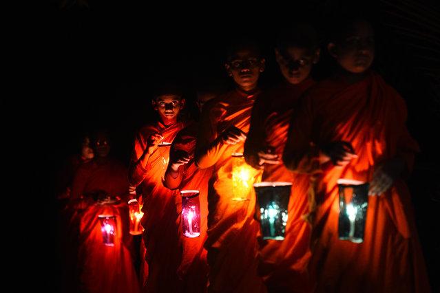 Buddhist nuns light paper lanterns on Vesak day, a festival also known as Buddha Jayanti to commemorate the birth, enlightenment, and death of Gautama Buddha, at the Dekanduwala  Bhikkhuni training centre in Horana on May 8, 2020. (Photo by Ishara S. Kodikara/AFP Photo)