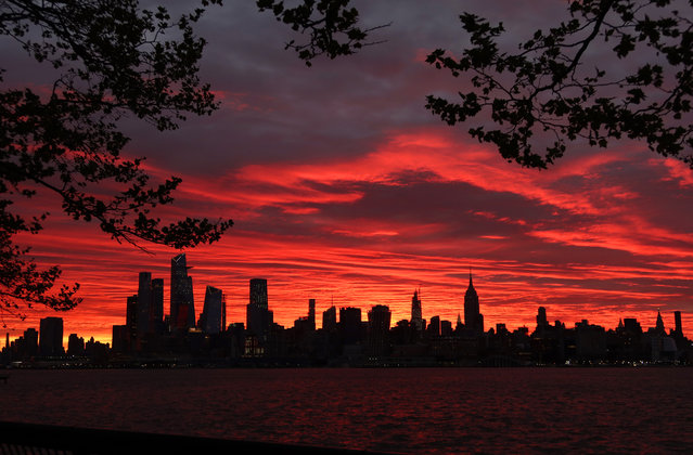 The sun rises behind the Empire State Building and Hudson Yards in New York City on May 6, 2020 as seen from Hoboken, New Jersey. (Photo by Gary Hershorn/Getty Images)