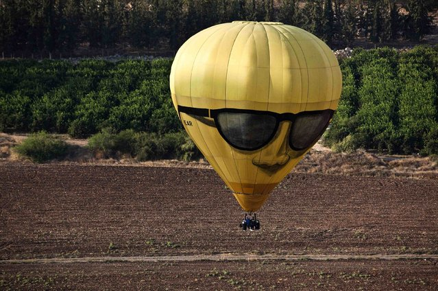 A hot air balloon flies close to the ground in the Jezreel Valley in northern Israel during an international hot air balloon festival October 14, 2014. (Photo by Nir Elias/Reuters)