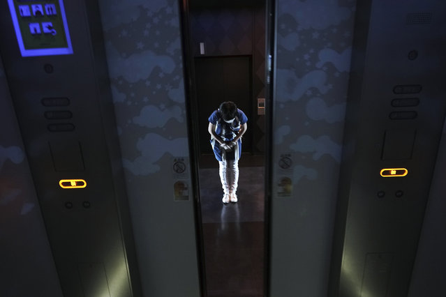 An employee wearing a protective mask and face shield to help curb the spread of the coronavirus bows guests as elevator doors close at a building Thursday, July 9, 2020, in Tokyo. (Photo by Eugene Hoshiko/AP Photo)