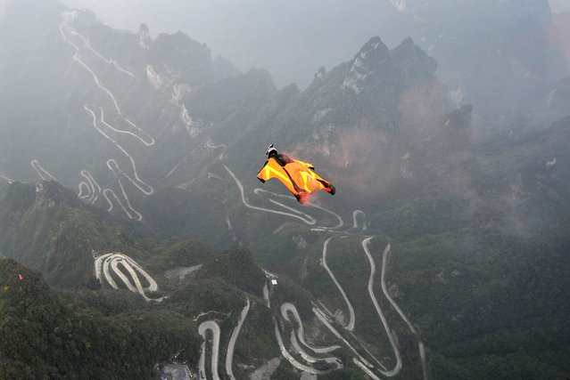 Wingsuit flyer contestant Melissa Pemberton of the U.S. jumps off a mountain at Tianmen Mountain National Park in Zhangjiajie, Hunan province October 19, 2014. (Photo by Reuters/China Daily)