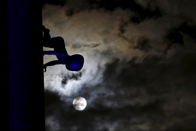 A supermoon is seen in the sky next to a statue of a baby in Prague, Czech Republic, September 28, 2015. Sky-watchers around the world were treated when the shadow of Earth cast a reddish glow on the moon, the result of rare combination of an eclipse with the closest full moon of the year. (Photo by David W. Cerny/Reuters)