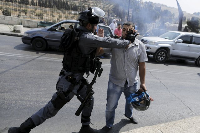 An Israeli policeman scuffles with a Palestinian man during clashes near the Arab East Jerusalem neighbourhood of Wadi al-Joz October 2, 2015. (Photo by Ammar Awad/Reuters)