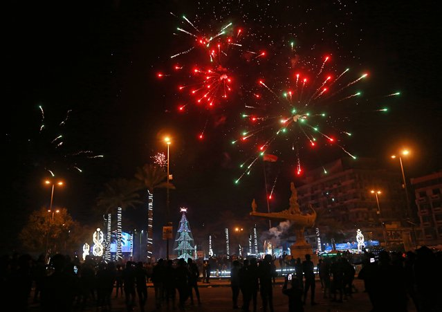 Iraqis watch fireworks explode during the New Year celebrations in Baghdad, Iraq, early Monday, January 1, 2018. (Photo by halid Mohammed/AP Photo/)