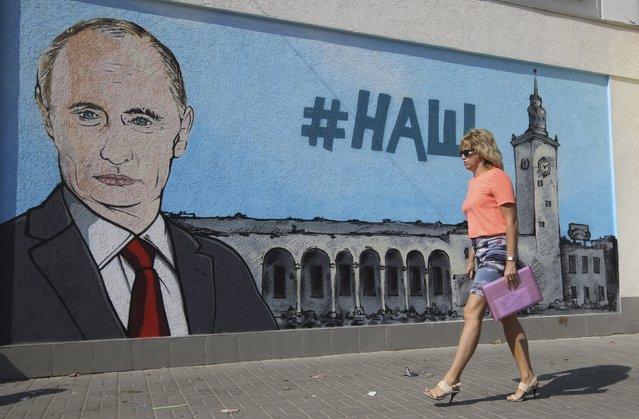 A woman walks past graffiti depicting Russian President Vladimir Putin in Simferopol, Crimea, August 17, 2015. (Photo by Pavel Rebrov/Reuters)