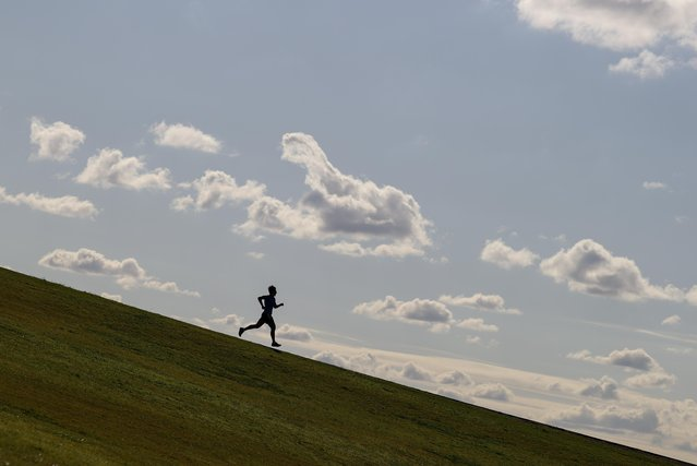 A runner exercises on a hill at Sydney Park amidst the easing of restrictions implemented to curb the spread of the coronavirus disease (COVID-19) in Sydney, Australia, June 26, 2020. (Photo by Loren Elliott/Reuters)