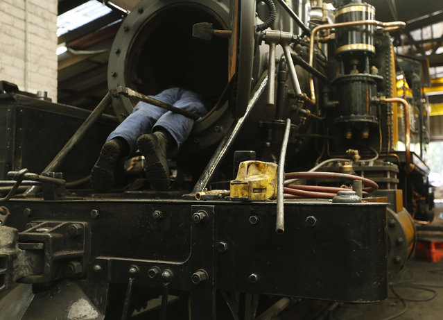 An engineer works inside the smokebox of a steam engine undergoing an overhaul in the Puffing Billy workshops at Belgrave Melbourne, October 20, 2014. (Photo by Jason Reed/Reuters)