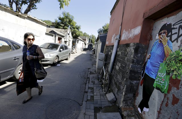 """A pedestrian looks at Chinese artist ROBBBB's work as she walks along a traditional alleyway, or """"hutong"""", in central Beijing September 25, 2015. (Photo by Jason Lee/Reuters)"""